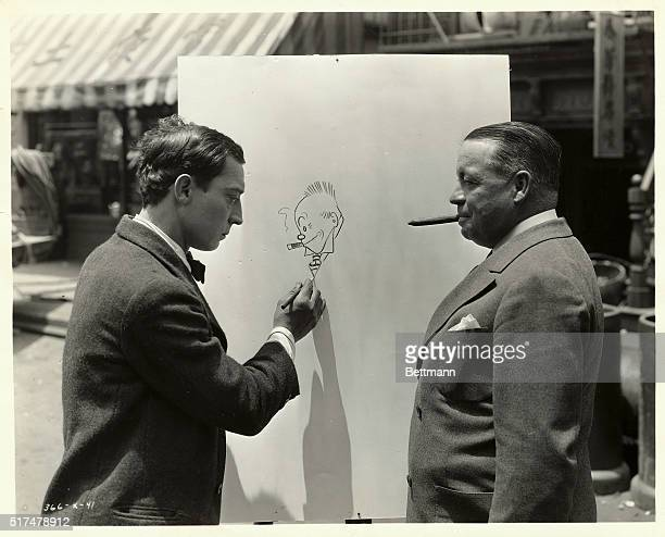 Buster Keaton pretends to work on a drawing actually started by cartoonist George McManus who poses so as to mimic his character Jiggs from the comic...