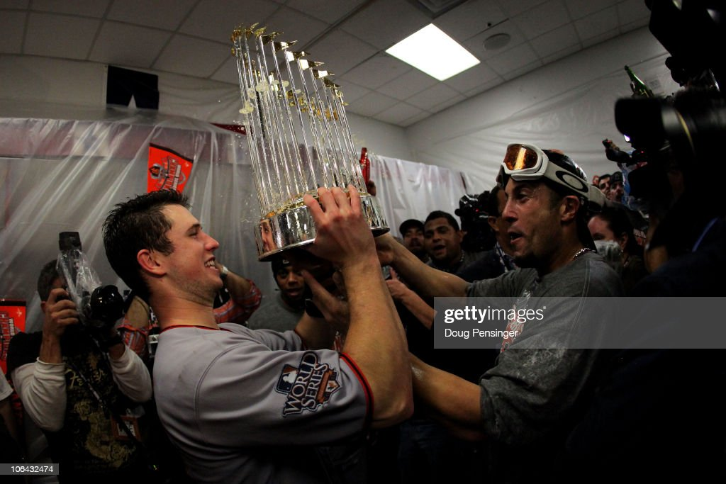 Buster Posey and Andres Torres of the San Francisco Giants celebrates with the trophy in the locker room after the Giants won 31 against the Texas...