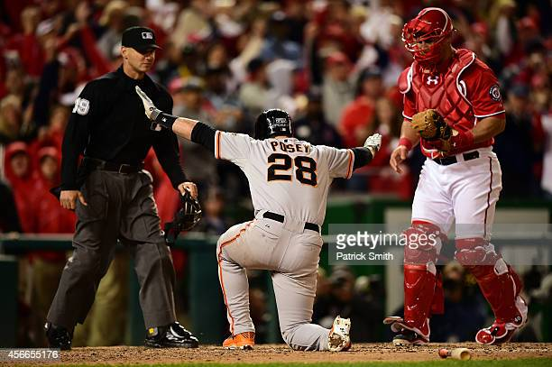 Buster Posey of the San Francisco Giants argues for a call of safe after being tagged out at home plate by Wilson Ramos of the Washington Nationals...