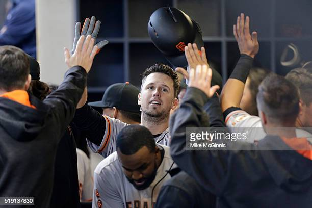 Buster Posey of the San Francisco Giants celebrates after hitting a solo home run in the eighth inning against the Milwaukee Brewers on Opening Day...