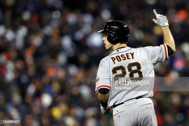 Buster Posey of the San Francisco Giants celebrates after scoring a two run home run to left field against Max Scherzer of the Detroit Tigers in the...