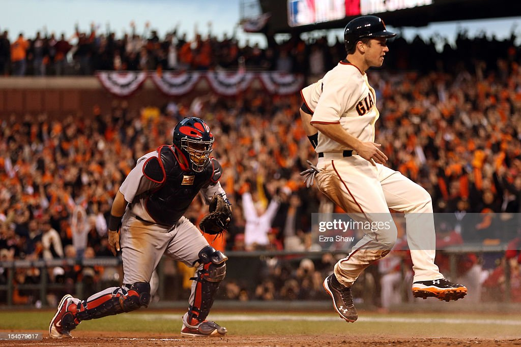 Buster Posey #28 of the San Francisco Giants celebrates after scoring in the third inning on a three-run double by Hunter Pence #8 against the St. Louis Cardinals in Game Seven of the National League Championship Series at AT&T Park on October 22, 2012 in San Francisco, California.
