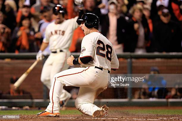 Buster Posey of the San Francisco Giants celebrates after scoring in the sixth inning against the Kansas City Royals during Game Four of the 2014...