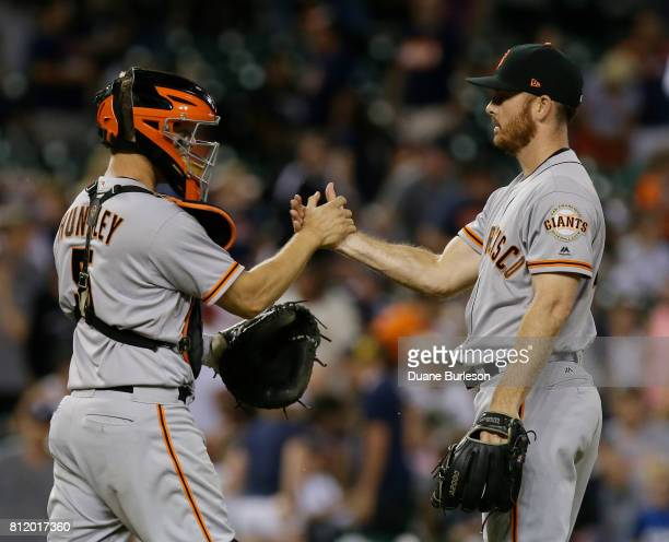Buster Posey of the San Francisco Giants congratulates closer Sam Dyson of the San Francisco Giants after a win over the Detroit Tigers at Comerica...