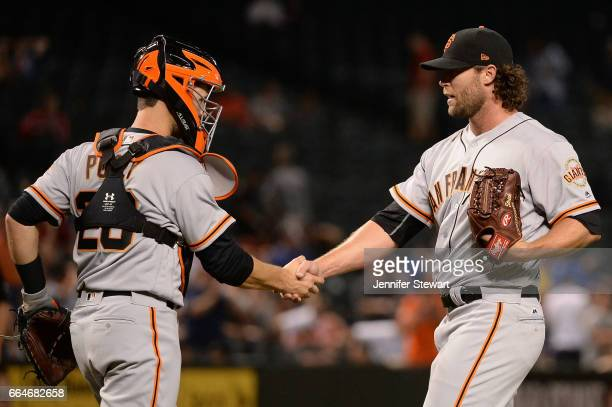 Buster Posey of the San Francisco Giants congratulates Hunter Strickland after closing out the game against the Arizona Diamondbacks at Chase Field...
