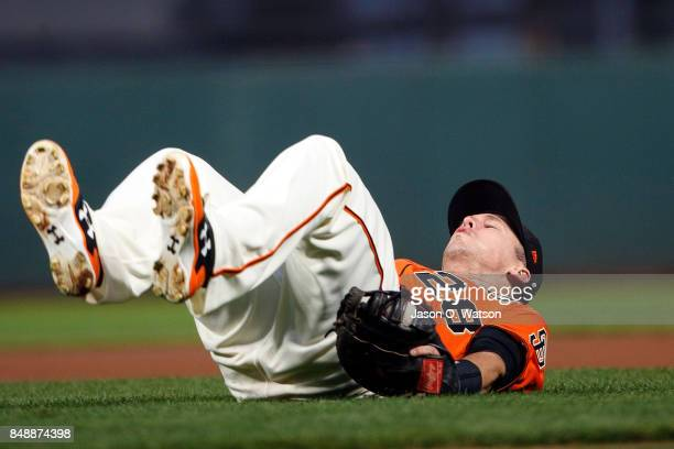 Buster Posey of the San Francisco Giants falls backwards after catching a fly ball hit off the bat of Jake Lamb of the Arizona Diamondbacks during...