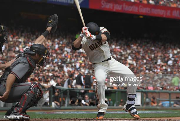 Buster Posey of the San Francisco Giants falls backwards after he was hit in the head with a pitch by Taijuan Walker of the Arizona Diamondbacks in...