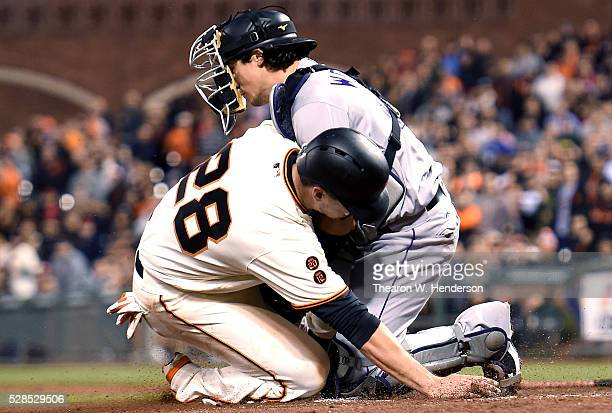 Buster Posey of the San Francisco Giants gets tagged out at home plate while colliding with catcher Tony Wolters of the Colorado Rockies in the...