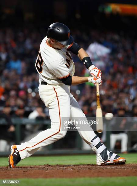 Buster Posey of the San Francisco Giants hits a single that scored Hunter Pence in the third inning against the Philadelphia Phillies at ATT Park on...