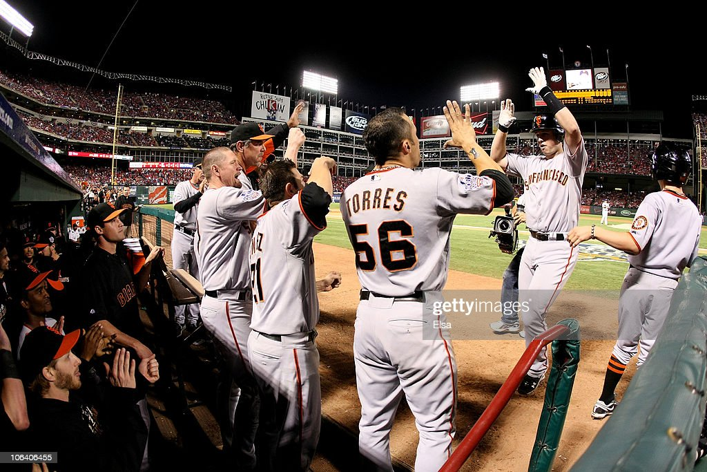 Buster Posey #28 (R) of the San Francisco Giants is congratulated by his teammates in the dugout after he scored on a solo home run in the eighth inning against the Texas Rangers in Game Four of the 2010 MLB World Series at Rangers Ballpark in Arlington on October 31, 2010 in Arlington, Texas.