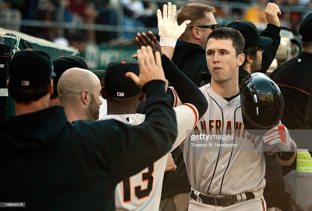 <a gi-track='captionPersonalityLinkClicked' href=/galleries/search?phrase=Buster+Posey&family=editorial&specificpeople=4896435 ng-click='$event.stopPropagation()'>Buster Posey</a> #28 of the San Francisco Giants is congratulated by teammates in the dugout after he hit a two-run home run in the seventh inning against the Oakland Athletics at O.co Coliseum on June 23, 2012 in Oakland, California.