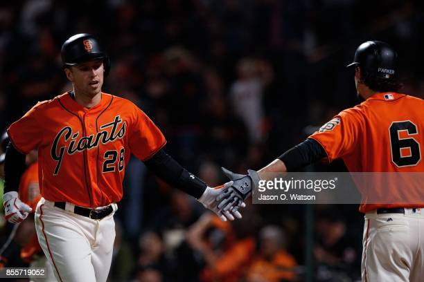 Buster Posey of the San Francisco Giants is congratulated by Jarrett Parker after scoring a run against the San Diego Padres during the first inning...