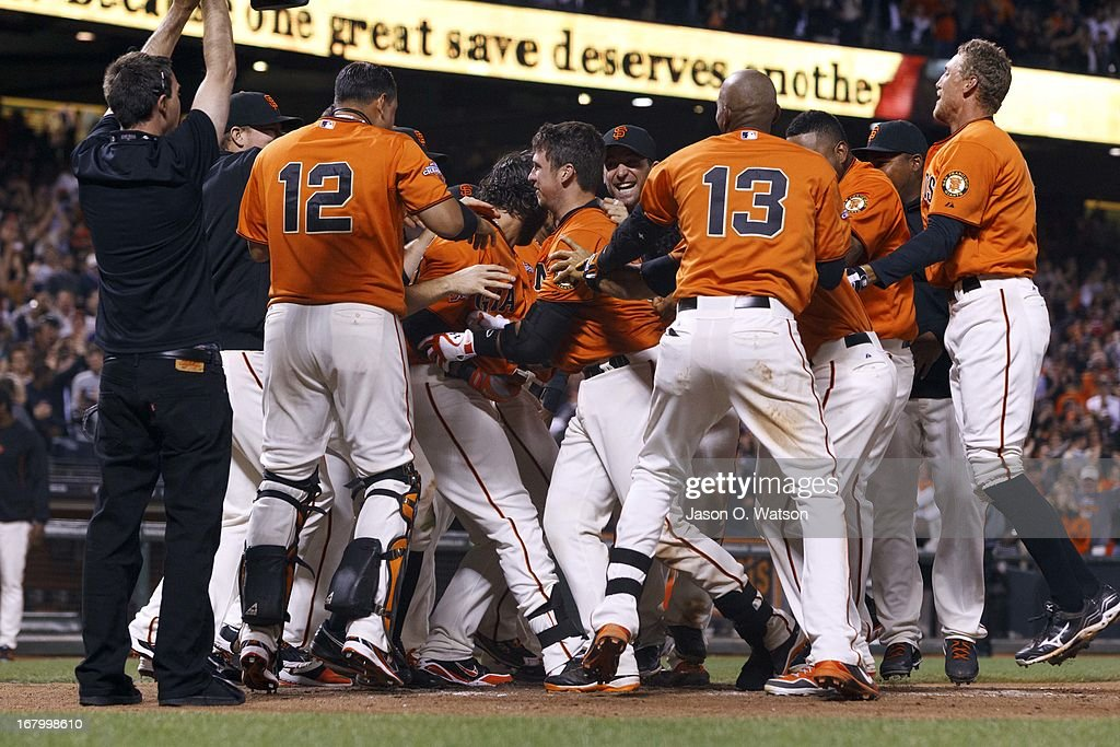 <a gi-track='captionPersonalityLinkClicked' href=/galleries/search?phrase=Buster+Posey&family=editorial&specificpeople=4896435 ng-click='$event.stopPropagation()'>Buster Posey</a> #28 of the San Francisco Giants (C) is mobbed by teammates at home plate after hitting a walk-off home run against the Los Angeles Dodgers at AT&T Park on May 3, 2013 in San Francisco, California. The Giants defeated the Dodgers 2-1.