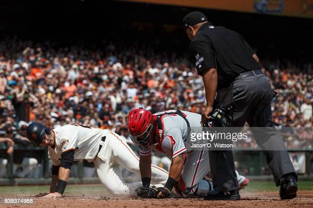 Buster Posey of the San Francisco Giants is tagged out at home plate by Jorge Alfaro of the Philadelphia Phillies in front of umpire Adrian Johnson...