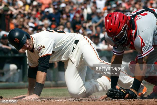 Buster Posey of the San Francisco Giants is tagged out at home plate by Jorge Alfaro of the Philadelphia Phillies during the second inning at ATT...