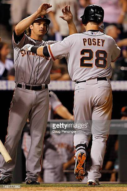 Buster Posey of the San Francisco Giants is welcomed home by Ryan Theriot of the San Francisco Giants after Posey's three run home run off of Matt...