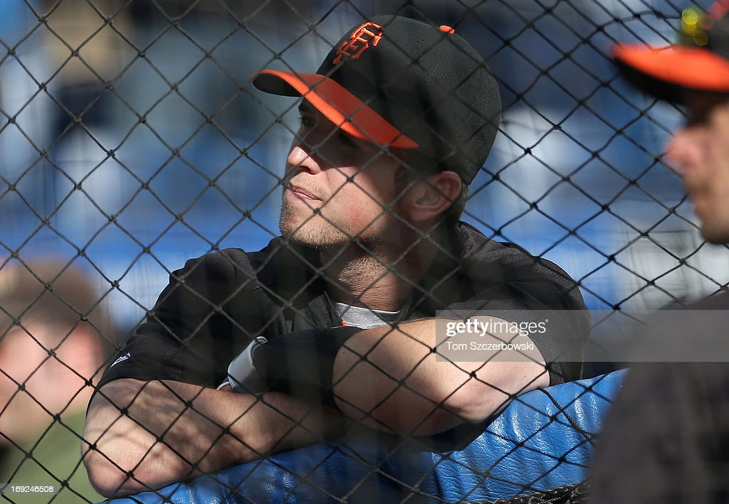 Buster Posey #28 of the San Francisco Giants looks on from behind the batting cage during batting practice before an MLB game against the Toronto Blue Jays on May 15, 2013 at Rogers Centre in Toronto, Ontario, Canada.