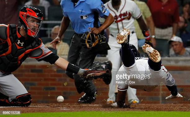 Buster Posey of the San Francisco Giants loses the ball as Johan Camargo of the Atlanta Braves slides safely into homeplate on a double hit by Ender...