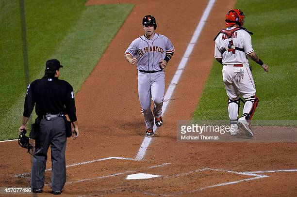 Buster Posey of the San Francisco Giants runs home to score on a sacrafice fly in the third inning against the St Louis Cardinals during Game One of...