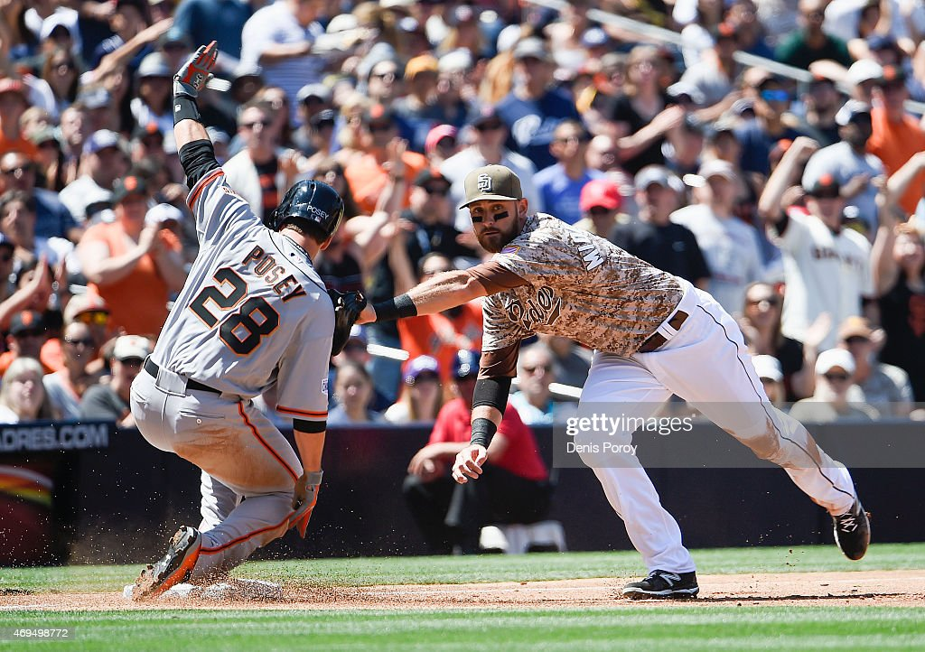 Buster Posey #28 of the San Francisco Giants slides safely into third base ahead of the tag of Will Middlebrooks #11 of the San Diego Padres during the third inning of a baseball game at Petco Park April 12, 2015 in San Diego, California.