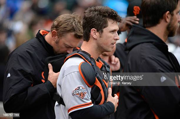 Buster Posey of the San Francisco Giants stands on the field during the singing of 'The Star Spangled Banner' before the game against the Chicago...