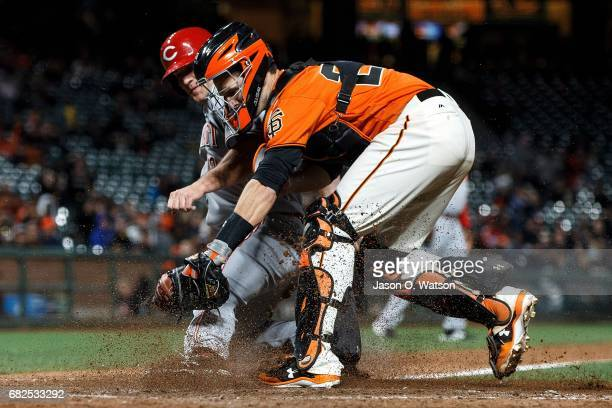 Buster Posey of the San Francisco Giants tags out Scott Schebler of the Cincinnati Reds at home plate during the fourteenth inning at ATT Park on May...
