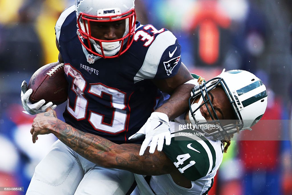 Buster Skrine #41 of the New York Jets tackles Dion Lewis #33 of the New England Patriots during the first half at Gillette Stadium on December 24, 2016 in Foxboro, Massachusetts.