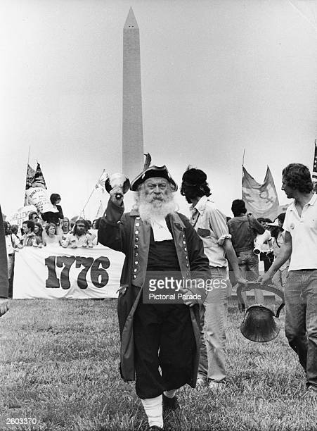 Buster Smith a member of the People's Bicentennial Commission rings a bell in costume during an antibig business protest with the Washington Monument...