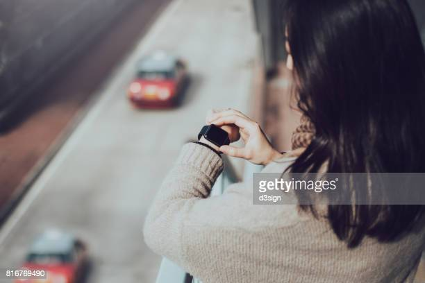 Busy businesswoman looking up time on smart watch in city street