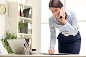 Beautiful Busy Businesswoman, standing in office, writing in planner and talking on mobile phone.