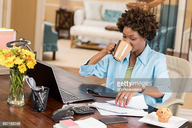 Busy businesswoman reviews documents while working from home