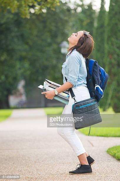 Collège étudiant tenant bien épais et une pile de livres sur le campus