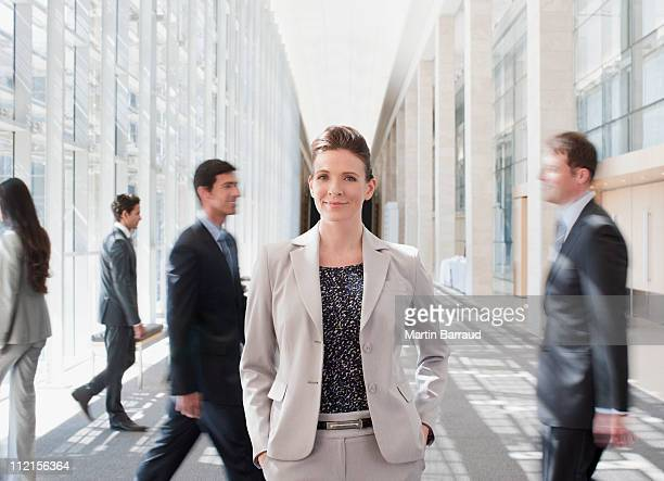 Busy co-workers waking past businesswoman
