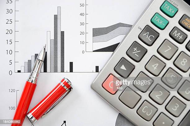 Busy desktop with graphic papers, red pen and calculator