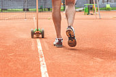 Man is painting necessary lines at tennis field. Close up of male legs. Copy space