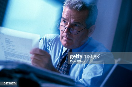 Busy mature (50s) executive in action in office setting.