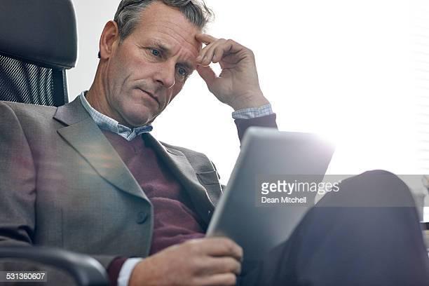 Busy mature man using digital tablet