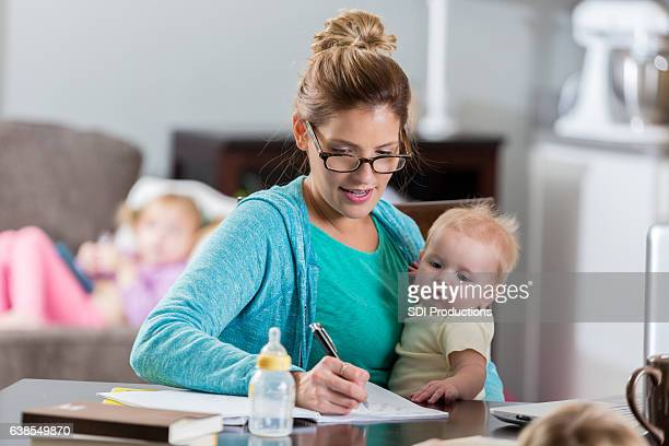 Busy mom studies while holding infant daughter