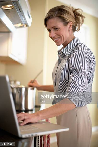 Busy Mother Cooking Dinner While Researching Online