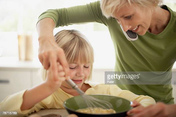 Busy Mother Helping Her Daughter to Cook