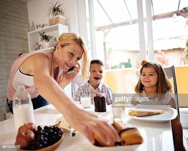 Busy Mother Organizing Children At Breakfast In Kitchen