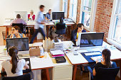 Wide Angle View Of Busy Design Office With Busy Workers At Desks Working.