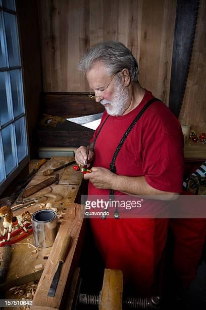 Santa Claus chargée de peinture dans l'atelier de Noël des jouets anciens