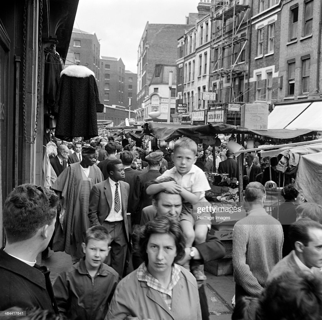 A busy scene in Middlesex Street part of the busy Petticoat Lane Market Whitechapel London c1946c1959 A woman and a child behind her being carried on...