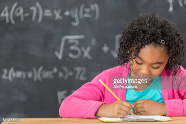 Busy schoolgirl works on assignment in front of chalkboard