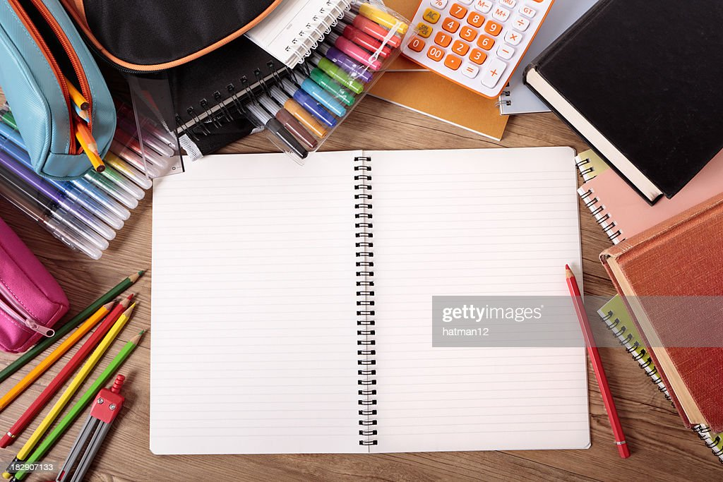 Busy student's desk with blank open notebook