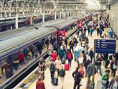 Horizontal color image of a busy railroad platform at Paddington station in London, UK.