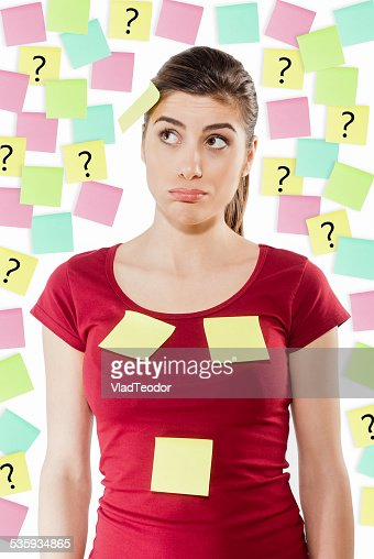 Busy woman against wall covered with colorful stickers : Stock Photo