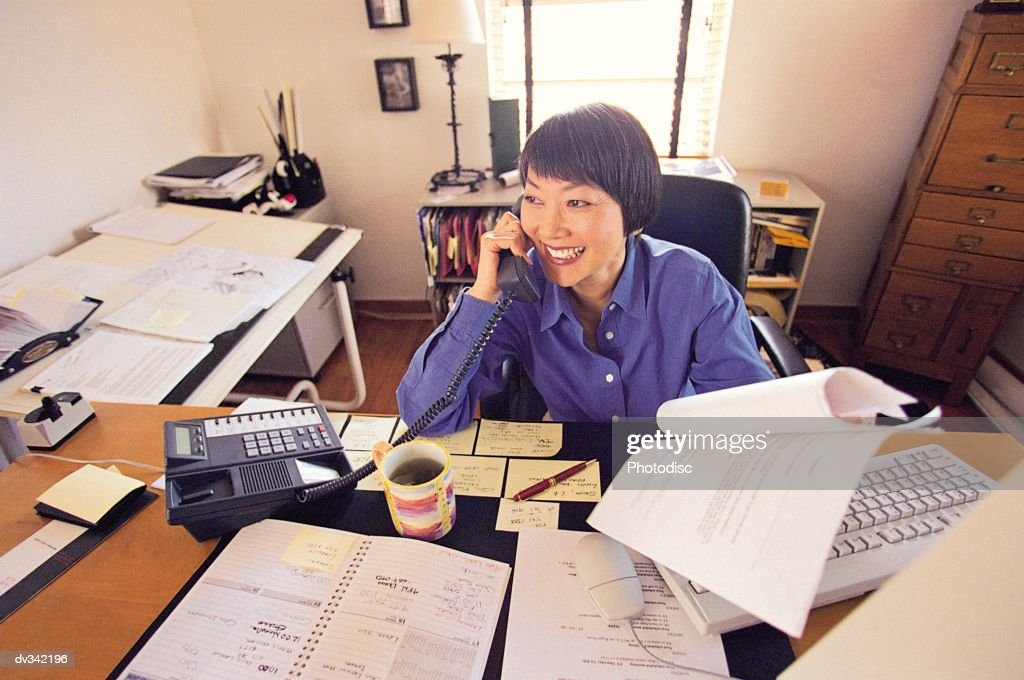 Busy woman at her desk : Stock Photo