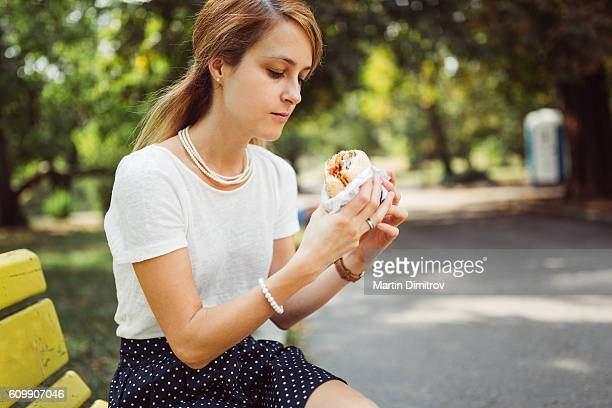 Busy woman eating hamburger outside the office